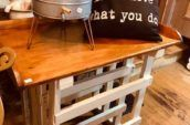 small wooden table with cold drinks container and black pillow on top