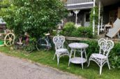 small white chairs and table beside bikes