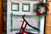and antique tricycle in front on an antique door with a Christmas wreath on it