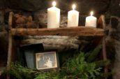 3 lit candles on an antique shelf