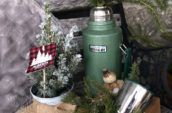 green thermos and box with tree branches inside them
