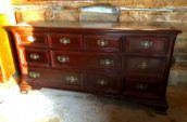 large cherry stained wooden dresser with gold handles