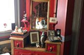 antique wooden dresser painted red with gold handles and a small centre mirror