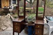 wooden vanity with gold handles and big mirrors