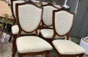 wooden chairs with white patterned pads on the back rest and seat