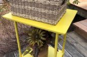 yellow wooden side table with whicker basket on top