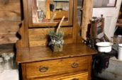 wooden dresser with medium sized mirror on top