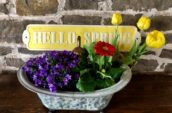 antique plant pot with yellow, red, and purple flowers