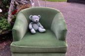 antique loveseat with a teddy bear on it