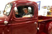 antique truck with a woman smiling in the driver's seat