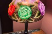lampshade with blue, purple and red flower design on top of wooden table