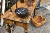 brown wooden table with bowl full of stones, 2 candle holders on top and basket on the floor
