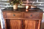 brown wooden cabinet with 2 top drawers, plant in a vase, candle and a hat on top of it.