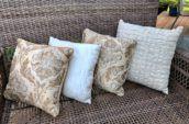 four throw pillows on a chair