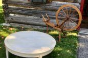 white round table with wooden cabin and wooden wheel in the background