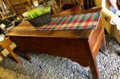 wooden table with checkered table cloth and plant on top