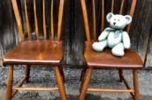 2 wooden chair with a stuffed bear on top of one of the chairs