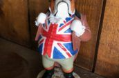 standing dog figurine wearing a hat, a coat, and United Kingdom's flag underneath