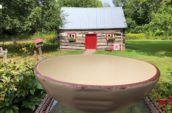 beige ceramic bowl on top of a table with wooden house in the background