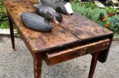 old wooden table with three duck figures on top
